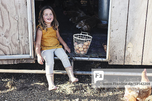 Full length of girl sitting in animal pen