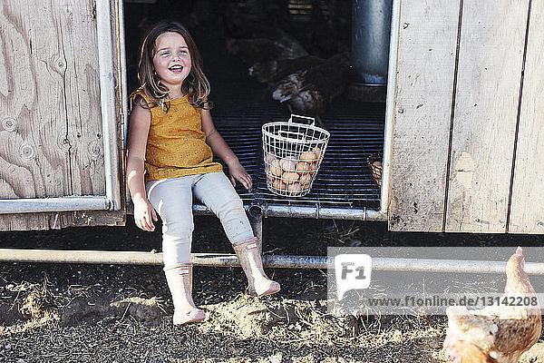 Full length of girl sitting in animal pen