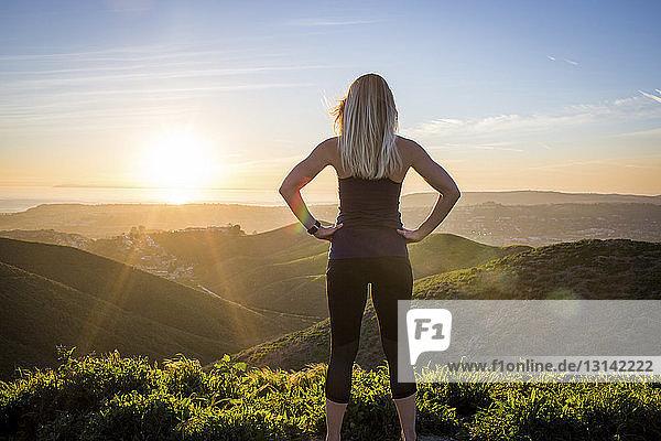 Rückansicht einer Frau  die bei Sonnenuntergang am Berg trainiert