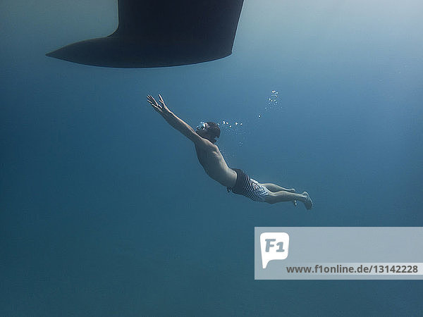 Full length of man swimming towards keel undersea