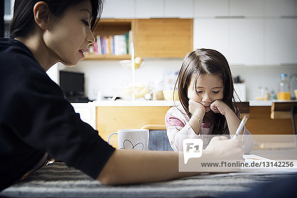Mother teaching daughter on table at home