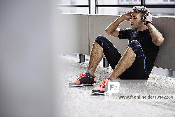 Männlicher Athlet mit Kopfhörern beim Entspannen auf dem Parkplatz