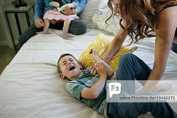 Glückliche Mutter kitzelt den Jungen zu Hause im Bett