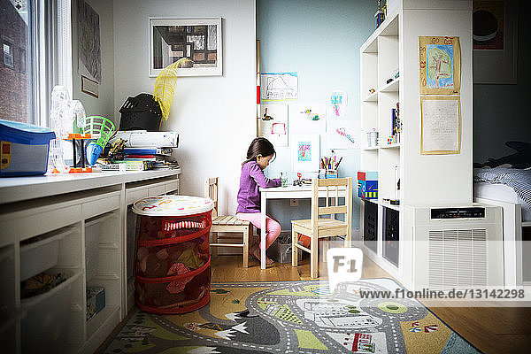 Girl studying on table in bedroom