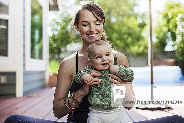 Portrait of cute baby with mother in backyard