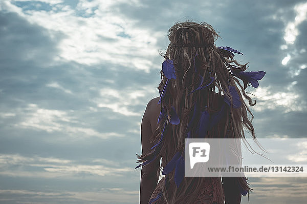 Rear view of woman with dread locks against cloudy sky