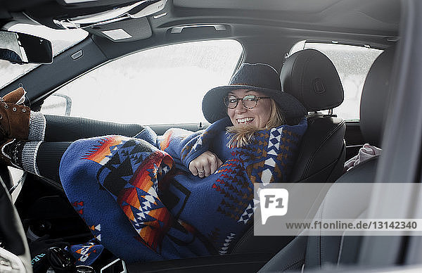 Portrait of happy woman wrapped in blanket looking through window while sitting in car