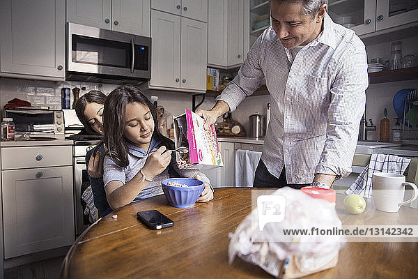 Father pouring breakfast cereal for daughter sitting on mother's lap in kitchen