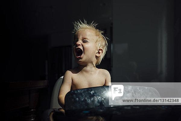 Kleiner Junge ohne Hemd schreit  während er die Brise der Klimaanlage in der Dunkelkammer zu Hause genießt