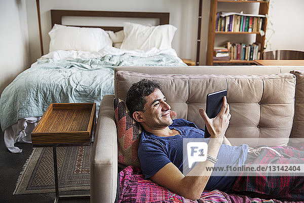 Smiling man using tablet computer while lying on sofa at home