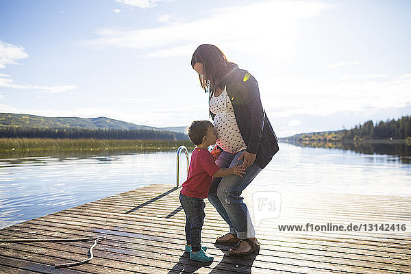 Side view of loving son kissing on pregnant mother's belly over lake against sky during sunny day