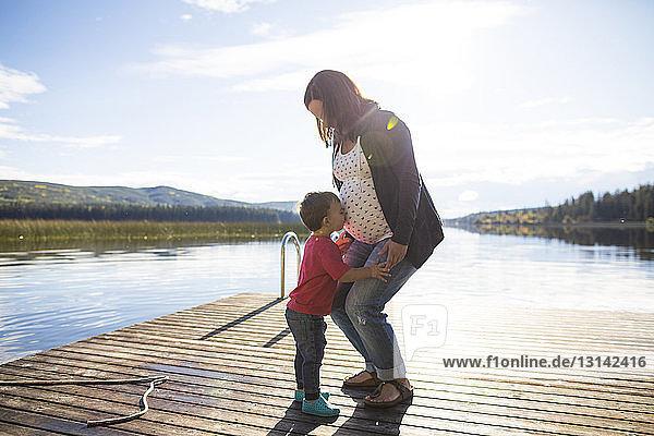 Seitenansicht eines liebenden Sohnes  der am sonnigen Tag auf den Bauch der schwangeren Mutter über dem See gegen den Himmel küsst