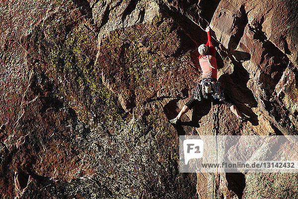 Rear view of female climber climbing mountain