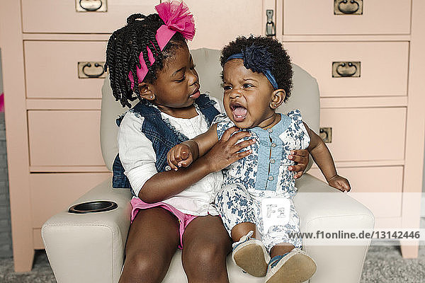 Kleines Mädchen schreit,  während es zu Hause mit seiner Schwester auf einem Stuhl sitzt