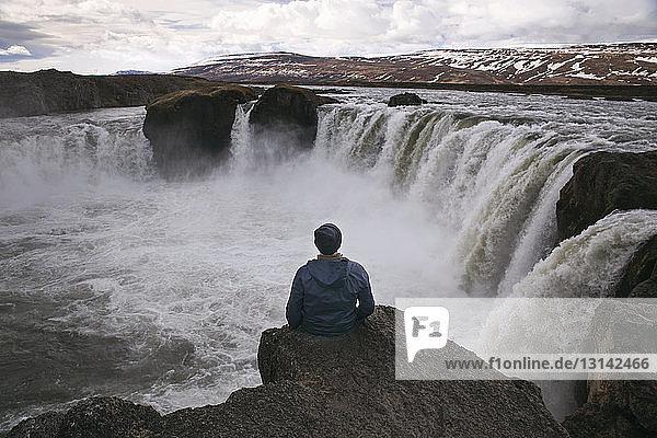 Rückansicht eines Mannes  der auf einer Klippe am Godafoss-Wasserfall sitzt
