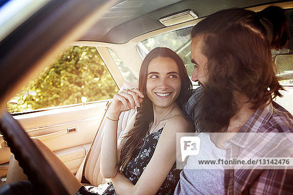 Happy couple looking at each other while sitting in pick-up truck