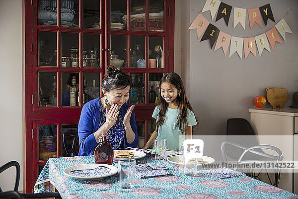 Surprised mother looking at pancakes made by daughter on birthday