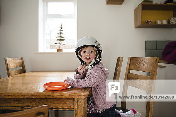 Portrait of girl wearing helmet eating food by table at home
