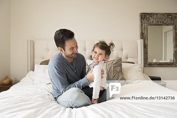 Porträt einer fröhlichen Tochter mit dem Vater zu Hause auf dem Bett sitzend