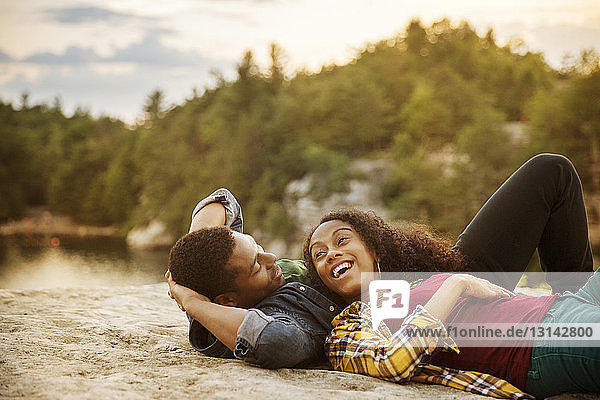 Happy couple lying on rock at lakeshore