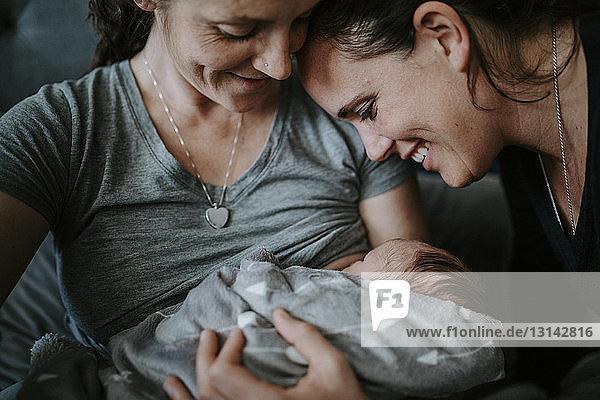 Nahaufnahme von lesbischen Müttern mit neugeborenem Sohn zu Hause im Bett