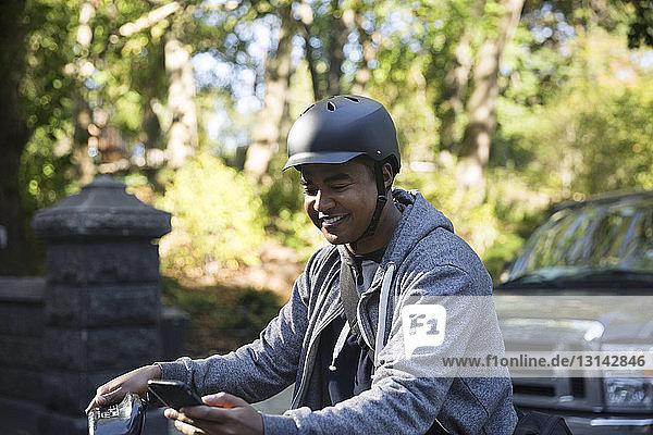 Glücklicher Mann mit Fahrrad  der auf der Straße in der Stadt ein Mobiltelefon benutzt