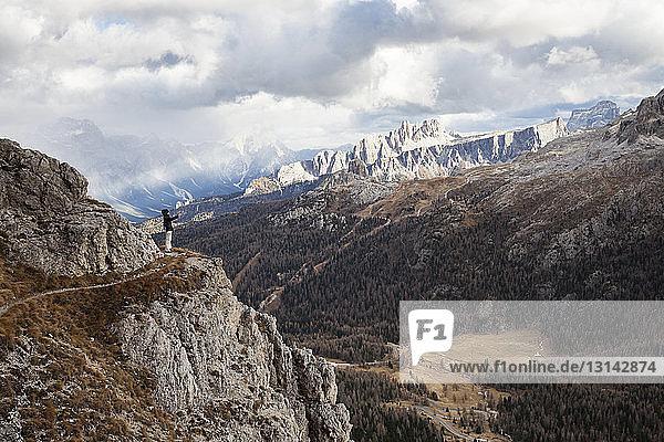 Weibliche Wanderin steht auf Berg vor bewölktem Himmel