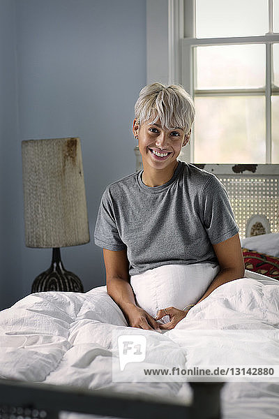 Portrait of happy young woman sitting on bed at home