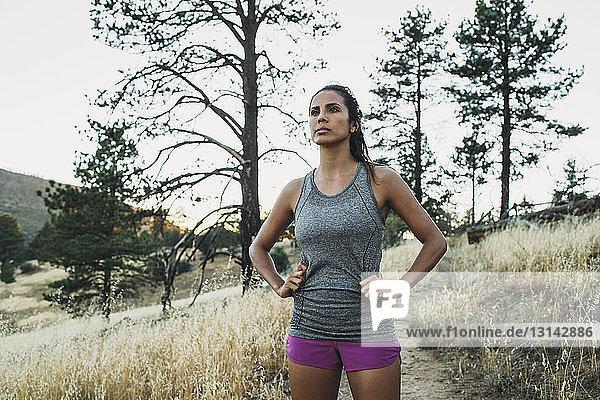Sportlerin steht mit den Händen auf der Hüfte auf einem Rasenplatz