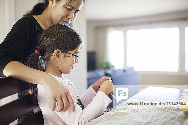 Frau betrachtet Tochter beim Wollstricken am Tisch