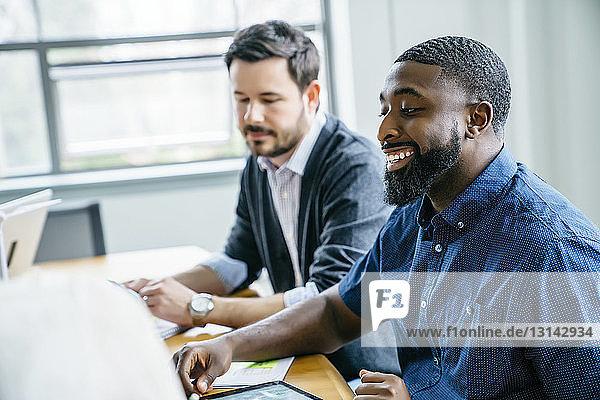Lächelnder Geschäftsmann sitzt neben seinem Amtskollegen