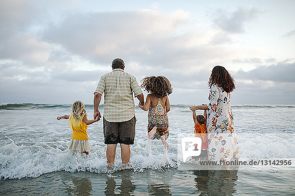 Rear view of family standing in sea at beach against cloudy sky