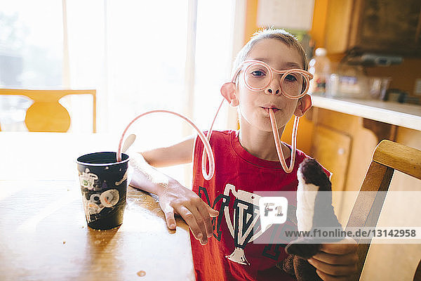 Portrait of boy drinking juice through straw glasses while holding stuffed toy at home