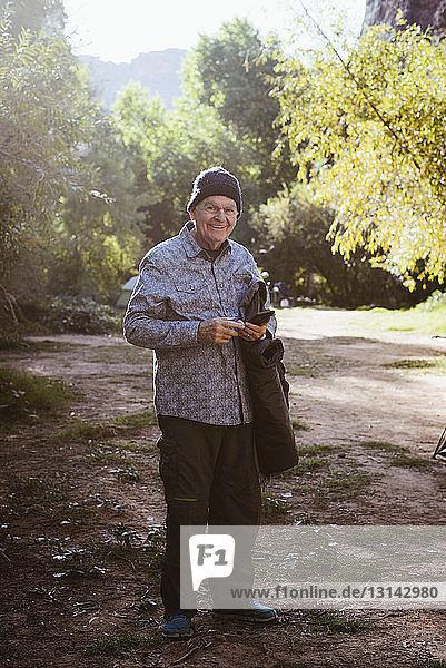 Porträt eines lächelnden Mannes auf einem Feld im Wald