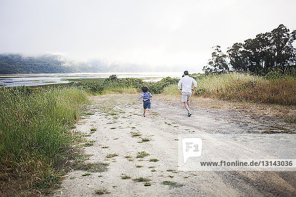 Rear view of father and son running on dirt road against sky