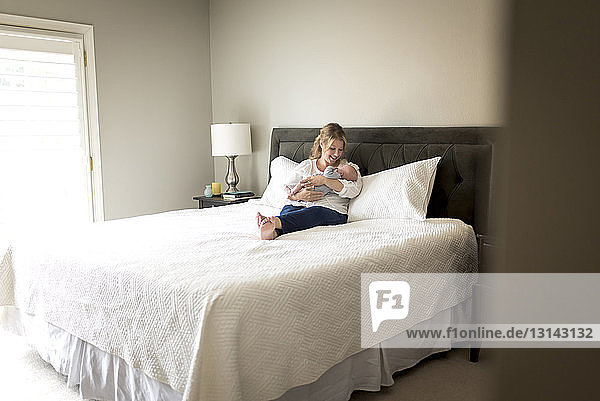 Mutter trägt Sohn  während sie zu Hause im Bett liegt