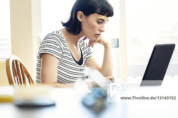 Seitenansicht einer Frau  die zu Hause am Laptop sitzt