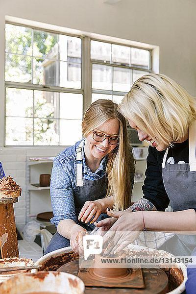 Frauen lächeln bei der Arbeit an der Töpferscheibe in der Werkstatt