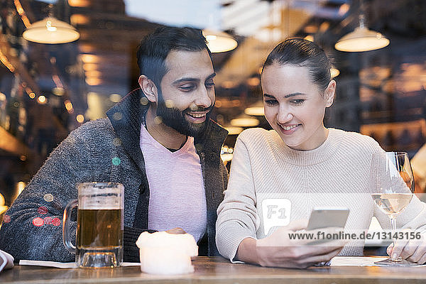 Woman with boyfriend using mobile phone seen through restaurant window