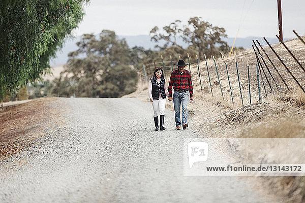 Paar hält sich beim Gehen auf unbefestigter Straße in voller Länge an den Händen