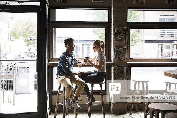 Lächelndes Paar trinkt Kaffee und unterhält sich an den Glasfenstern eines Cafés
