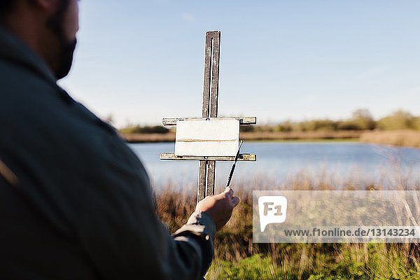 Midsection of painter painting lake on canvas against sky