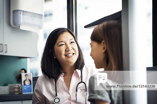 Lächelnde Ärztin misst in der Klinik die Grösse eines Mädchens