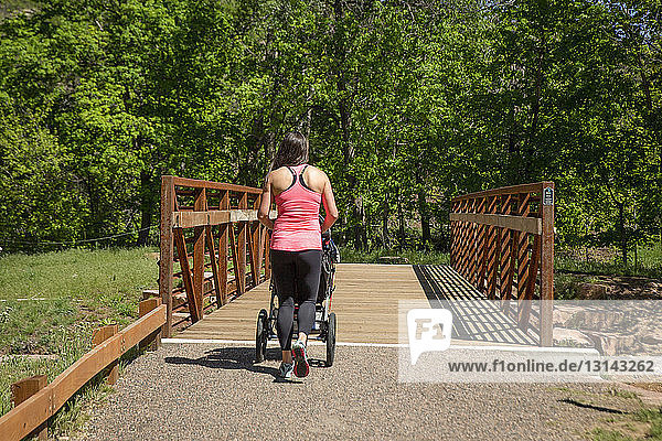 Rear view of woman with baby stroller walking at park during sunny day