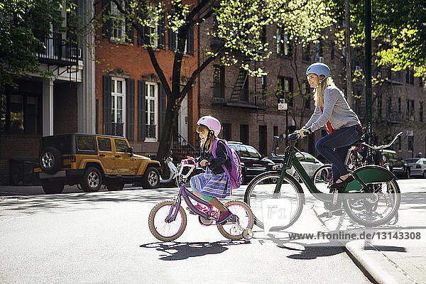 Mother and daughter riding bicycles on street