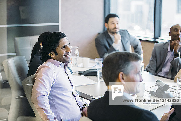 Colleagues discussing in board room at office