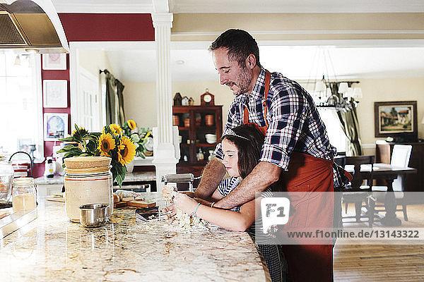 Seitenansicht von Vater und Tochter beim Kneten des Nudelteigs auf der Kücheninsel