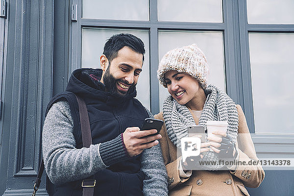 Man showing mobile phone to girlfriend while leaning by building in city