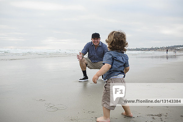 Father and son playing on shore against sky at beach