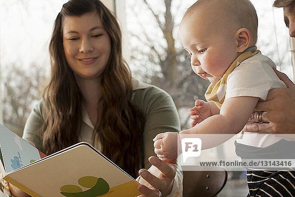Mutter zeigt dem Baby zu Hause ein Bilderbuch